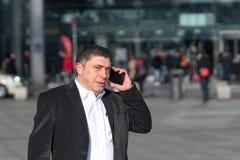 商人谈话在智能手机 免版税库存图片