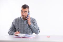 年轻商人谈话在电话和举行 免版税库存图片
