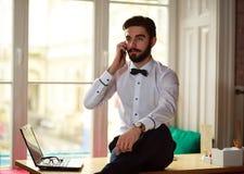 年轻商人谈话在电话在办公室 免版税库存图片