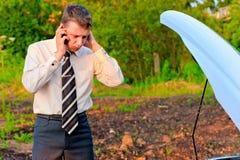 商人谈话在电话在残破的汽车附近 免版税库存图片