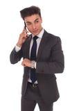 年轻商人谈话在电话检查时间 免版税图库摄影