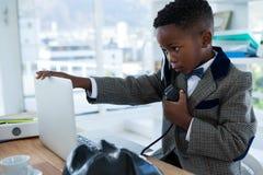 商人谈话在电话,当接触膝上型计算机时 库存照片