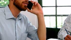 商人谈话在笔记薄的手机和同事文字 股票视频