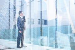 商人谈话由在办公室、通信或者成功概念的手机 免版税库存图片