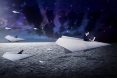 商人赛跑与去为更好的事业的纸飞机 库存照片