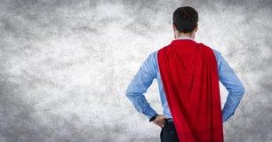 商人超级英雄用在臀部的手反对白色背景和难看的东西覆盖物 免版税库存照片
