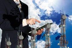 商人运转的片剂、蓝天和世界地图, telecommuni 免版税图库摄影