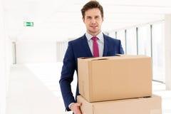 年轻商人运载的纸板箱画象在新的办公室 免版税库存图片
