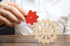 商人连接一个小红色齿轮到一个大链轮 建立商业运作和通信象征主义  免版税库存图片