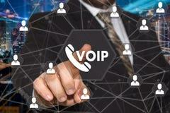 商人选择在触摸屏上的VOIP按钮有未来派背景 概念VOIP 库存图片