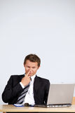 商人采摘鼻子,看膝上型计算机在办公室 免版税库存图片