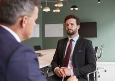 商人采访的男性候选人毕业生补充评估天在办公室 库存图片