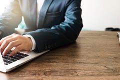 商人键入的键盘膝上型计算机的手在木桌上的 库存图片