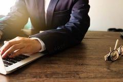 商人键入的键盘膝上型计算机的手在木桌上的 库存照片