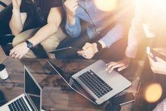 年轻商人队分析财务网上报告现代电子小配件 工友起始的数字式项目 免版税库存照片