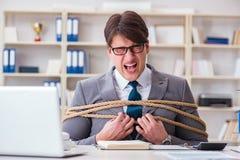商人阻塞与绳索在办公室 免版税库存图片