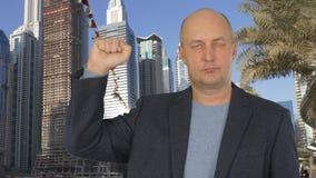 商人陈列握紧了拳头在城市大厦背景的右手 股票录像
