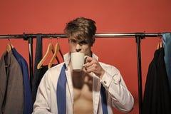 商人饮料茶或咖啡在衣橱在红色背景 免版税图库摄影