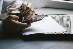 商人饮用的咖啡和使用便携式计算机和MOBIL 免版税库存照片