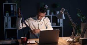 商人饮用的咖啡和后研究膝上型计算机在夜 股票视频