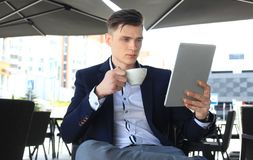商人饮用的咖啡和读新闻在咖啡馆 免版税库存图片