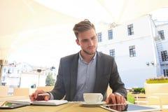 商人饮用的咖啡和读新闻在咖啡馆 图库摄影