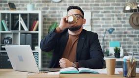 商人饮用的咖啡的快动作与膝上型计算机一起使用在办公室 股票录像