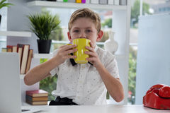 商人饮用的咖啡画象从黄色杯子的在书桌 免版税图库摄影