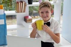 商人饮用的咖啡画象从黄色杯子的由膝上型计算机 免版税库存图片
