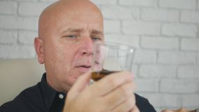 商人饮用的威士忌酒和抽烟的雪茄 免版税库存图片