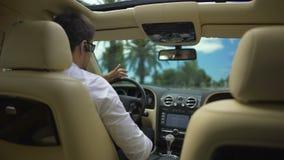 商人驾驶汽车和谈话在无线耳机,技术的电话 影视素材