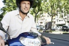 商人骑马小型摩托车 免版税图库摄影
