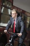 年轻商人骑马自行车乘公共汽车 免版税图库摄影