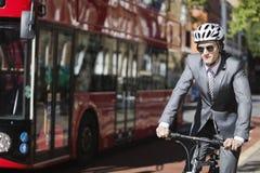 年轻商人骑马自行车乘在街道上的公共汽车 免版税库存图片