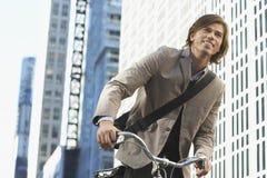 商人骑马自行车在街市区 免版税库存照片