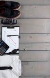 商人,在灰色木背景的工作成套装备 有半正式礼服的白色衬衣,手表,传送带,牛津鞋子, planchette 库存图片