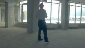 商人,地产商,安全帽的投资者走在未完成的大厦的 在建设中里面的摩天大楼 影视素材