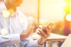 商人,智能手机,膝上型计算机,日落概念 免版税库存图片