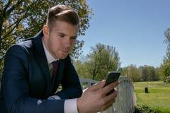 商人,蓝色衣服的执行委员使用机动性,手机在公园 免版税库存图片