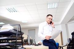商人读一个文件在办公室和谈话在mobi 图库摄影