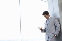 商人读书在手机的正文消息 免版税库存照片