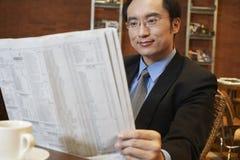 商人读书报纸在咖啡馆表上 免版税库存照片