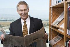 商人读书报纸在图书馆里 免版税库存图片