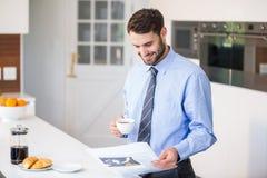 商人读书报纸,当喝咖啡时 免版税库存图片