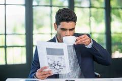 商人读书报纸,当食用咖啡时 库存图片