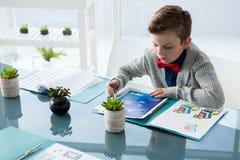 商人读书文件大角度看法,当坐在书桌时 免版税库存照片