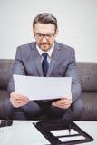 商人读书文件,当坐沙发时 免版税库存照片