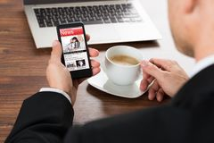 商人读书新闻,当食用咖啡时 免版税图库摄影