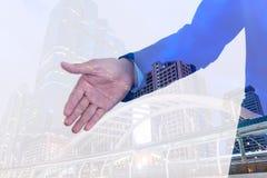 商人延伸的手两次曝光对震动有城市背景 免版税库存图片