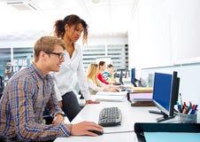 商人年轻多种族计算机书桌 免版税库存照片